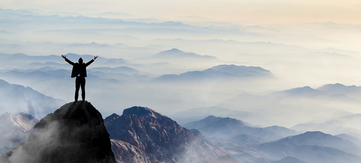 Home page slider image showing man on top of mountain with arms triumphantly thrown in the air